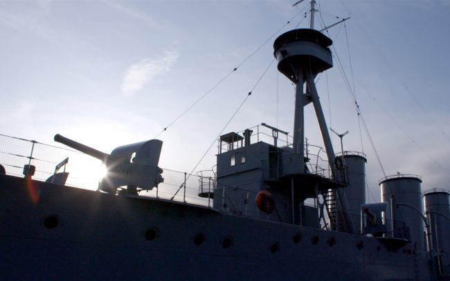A warship silhouetted against the sun.